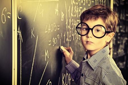 교실에서 칠판에 쓰기 둥근 안경에 귀여운 소년의 초상화.