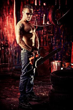 古いガレージでハンサムな筋肉の男の肖像画。