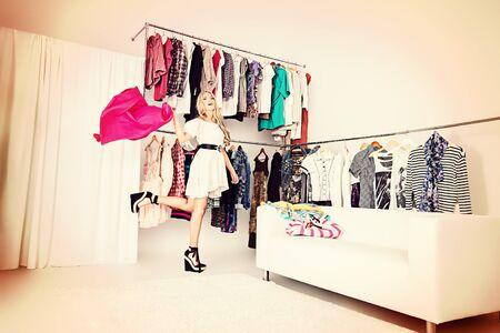 ファッショナブルな若い女性の衣料品店でのショッピングします。