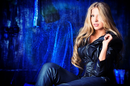 Stunning blonde woman in black leather jacket in the old garage.