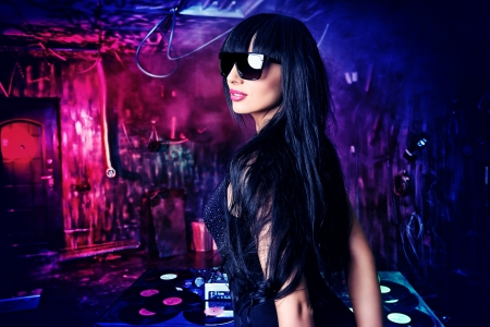 Beautiful sexy DJ girl working on a party in the old garage. Stock Photo