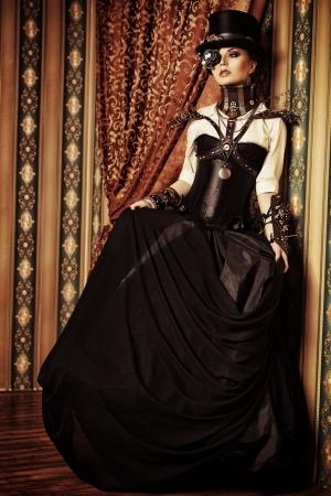 Full length portrait of a beautiful steampunk woman over vintage background. Reklamní fotografie