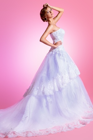 Full length portrait of a beautiful charming bride in a luxurious dress. Over pink background. Stock Photo - 21774358