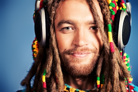 Portrait of a happy rastafarian young man listening to music in headphones. Stock Photo