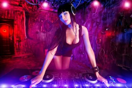 오래된 차고 파티에 근무하는 아름 다운 섹시 DJ 소녀. 스톡 콘텐츠