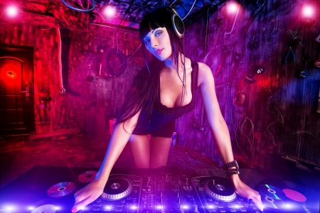 Mooie sexy DJ meisje werkt op een feestje in de oude garage.