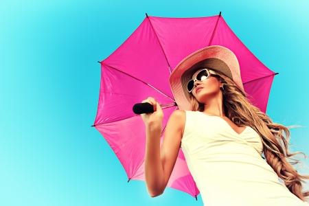 Mooie jonge vrouw in elegante hoed en zonnebril bedrijf paraplu op sky. Stockfoto