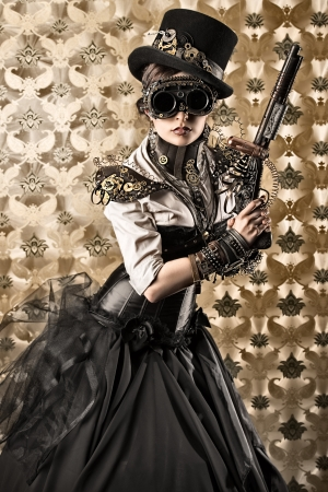 ビンテージ背景の上に銃を保持して美しいスチーム パンクな女性の肖像画。