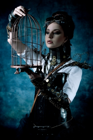 Portrait of a beautiful steampunk woman with a cage over grunge background.