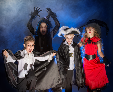 Cheerful children in halloween costumes posing over dark background. Stok Fotoğraf
