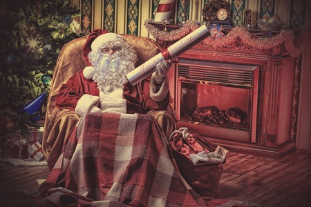 Santa Claus with a list of Christmas presents sitting in a comfortable chair near the fireplace at home. Stock Photo - 22450072