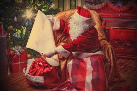 Kerstman met een lijst van kerstcadeaus zitten in een comfortabele stoel bij de open haard thuis.
