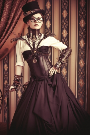 Full length portrait of a beautiful steampunk woman over vintage background. Stock Photo