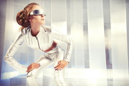 銀のラテックス衣装と未来的なヘアスタイルとメイクアップ眼鏡の美しい若い女性。サイエンス フィクションのスタイルです。