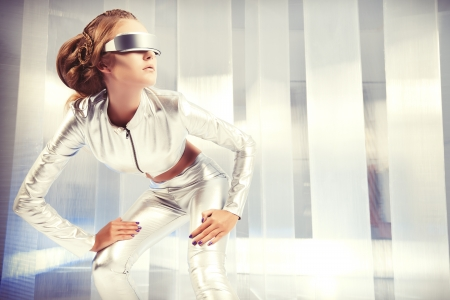 Beautiful young woman in silver latex costume and glasses with futuristic hairstyle and make-up. Sci-fi style. 版權商用圖片 - 22682911