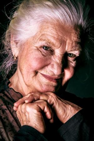 Portret van een gelukkige senior vrouw lachend op de camera. Over zwarte achtergrond.