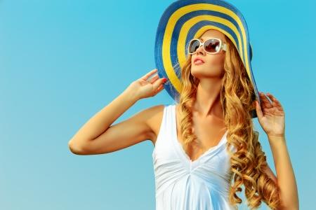 Schöne junge Frau in eleganten Hut und Sonnenbrille posiert über Himmel. Standard-Bild - 22854648