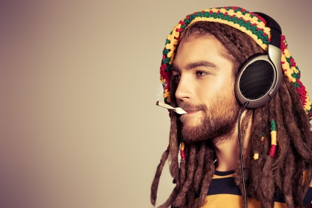 Portrait of a happy rastafarian young man listening to music in headphones