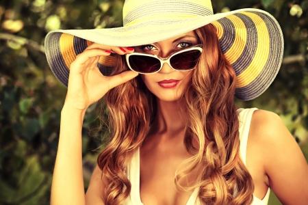 Mooie jonge vrouw in elegante hoed en zonnebril poseren buiten.