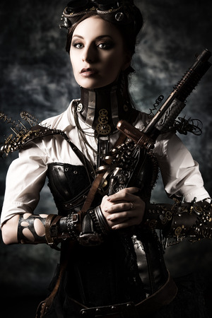 Portrait of a beautiful steampunk woman holding a gun over grunge background. Stock Photo - 23199837