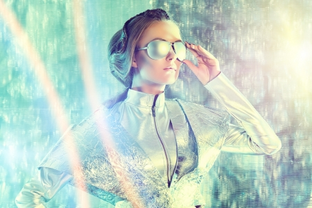 Beautiful young woman in silver latex costume and glasses with futuristic hairstyle and make-up. Sci-fi style.