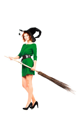 Full length portrait of a charming red-haired witch with broom. Halloween. Isolated over white.