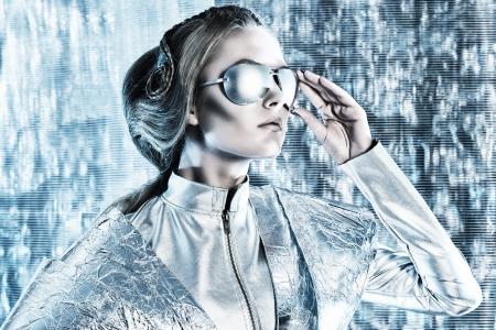 Mooie jonge vrouw in zilver latex kostuum en glazen met futuristische kapsel en make-up. Sci-fi stijl.