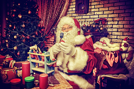 Santa Claus making Christmas gifts at home.