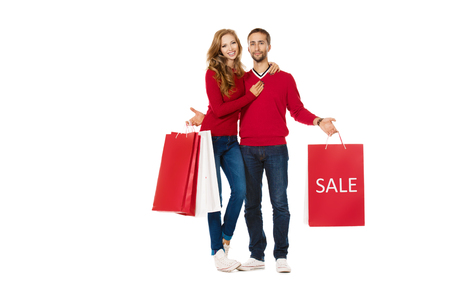 Happy young couple standing with a lot of shopping bags. Sale. Isolated over white.