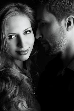 暗闇の中でスタジオでポーズ恋に美しい若いカップルの肖像画。