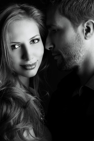 Portrait of a beautiful young couple in love posing at studio over dark . Stock Photo