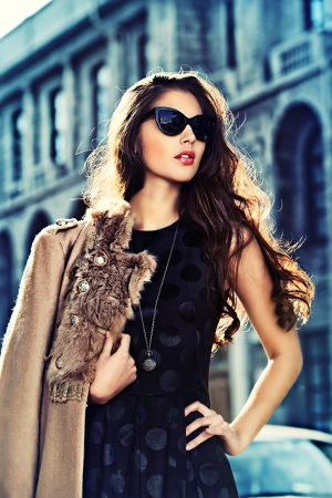 Attractive modern woman standing on the city street. Imagens