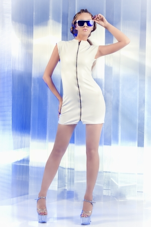 Futuristic young woman in white latex dress calling by cell phone. Sci-fi style. Stok Fotoğraf