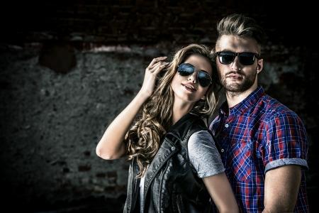 Paar van jonge mensen in jeans kleding poseren buitenshuis over bakstenen muur. Stockfoto