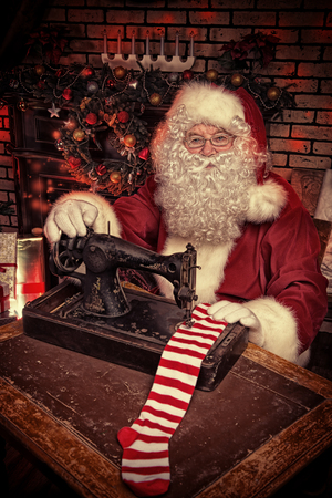 Santa Claus is sewing on a sewing machine striped socks for Christmas. Stock Photo