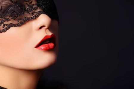 黒いレースのマスクで魅力的な女性のクローズ アップの肖像画。