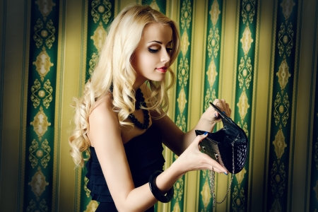 Beautiful blonde woman looking into her purse.  Imagens