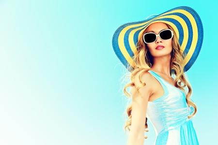 Prachtige jonge vrouw in elegante hoed en zonnebril poseren over hemel. Stockfoto