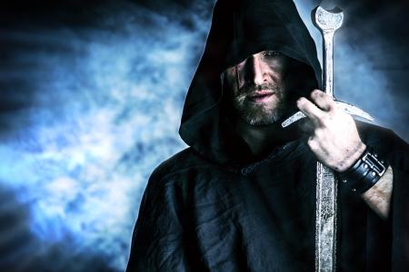 Portret van een moedige strijder zwerver in een zwarte mantel en zwaard in de hand. Historische fantasie. Stockfoto