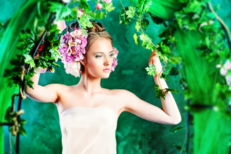 Beautiful young woman standing under an arch of flowers and overgrown loach. Magic of the spring. Stock Photo - 25228037