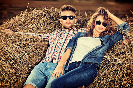 Romantic young couple in casual clothes sitting together in haystack.