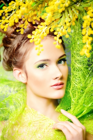 Portrait of a beautiful girl with mimosa flowers. Spring. Stock Photo