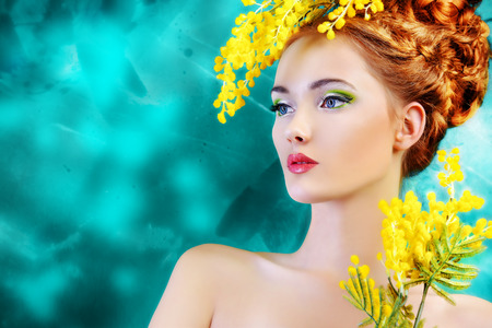 Portrait of a beautiful girl with mimosa flowers