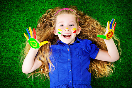 Laughing little girl painted in bright colors lying on green grass. Happy childhood. Stock Photo