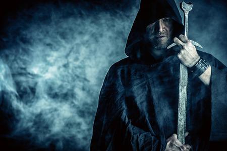 Retrato de un guerrero valiente trotamundos en un manto negro y una espada en la mano. Fantasía histórica. Foto de archivo - 26145187