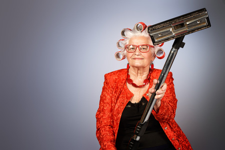 Elderly woman in curlers with a vacuum cleaner looking at camera.