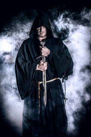 黒マントと剣手の勇敢な戦士の放浪者の肖像画。歴史的なファンタジー。