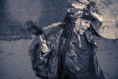 Portrait eines Schamanen tanzen mit einer Trommel im Freien. Schwarz-weiß.