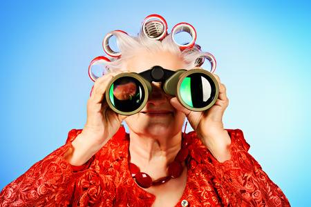 Portret van een bejaarde vrouw in krulspelden vooruit kijken door een verrekijker. Stockfoto
