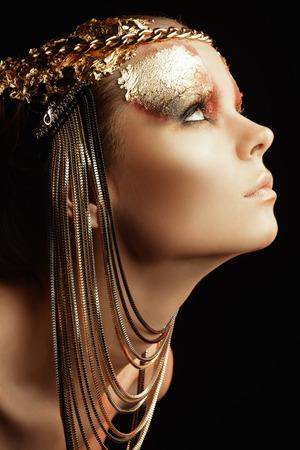 アート プロジェクト: 黄金のメイクアップと美しい女性。ジュエリー、メイクアップ。ファッション。黒の背景。